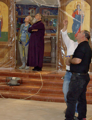 Archbishop Elias Chacour and Sr Bernadette, in scaffold harness,discuss the dome icon, together with Micha and Walid