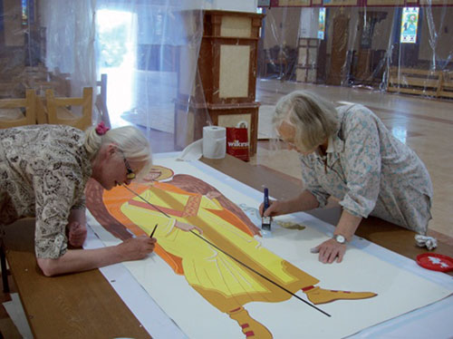 Audrey Porksen and Sr. Bernadette painting the background of the sixteen angels to surround the drum of the dome